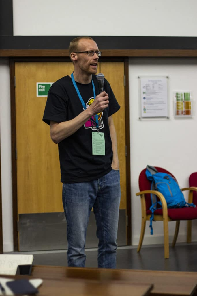 Mark Wilkinson MC at WordCamp Bristol, holding a microphone speaking to the audience.