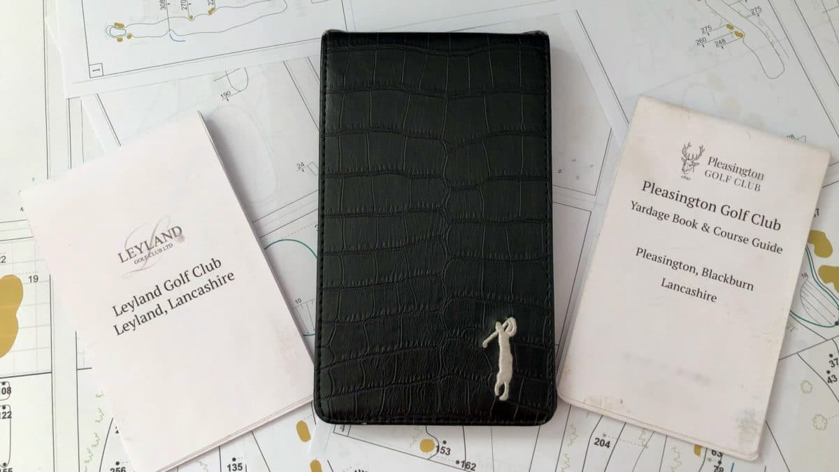 Hand made golf yardage books along side a score card holder, viewed from above.
