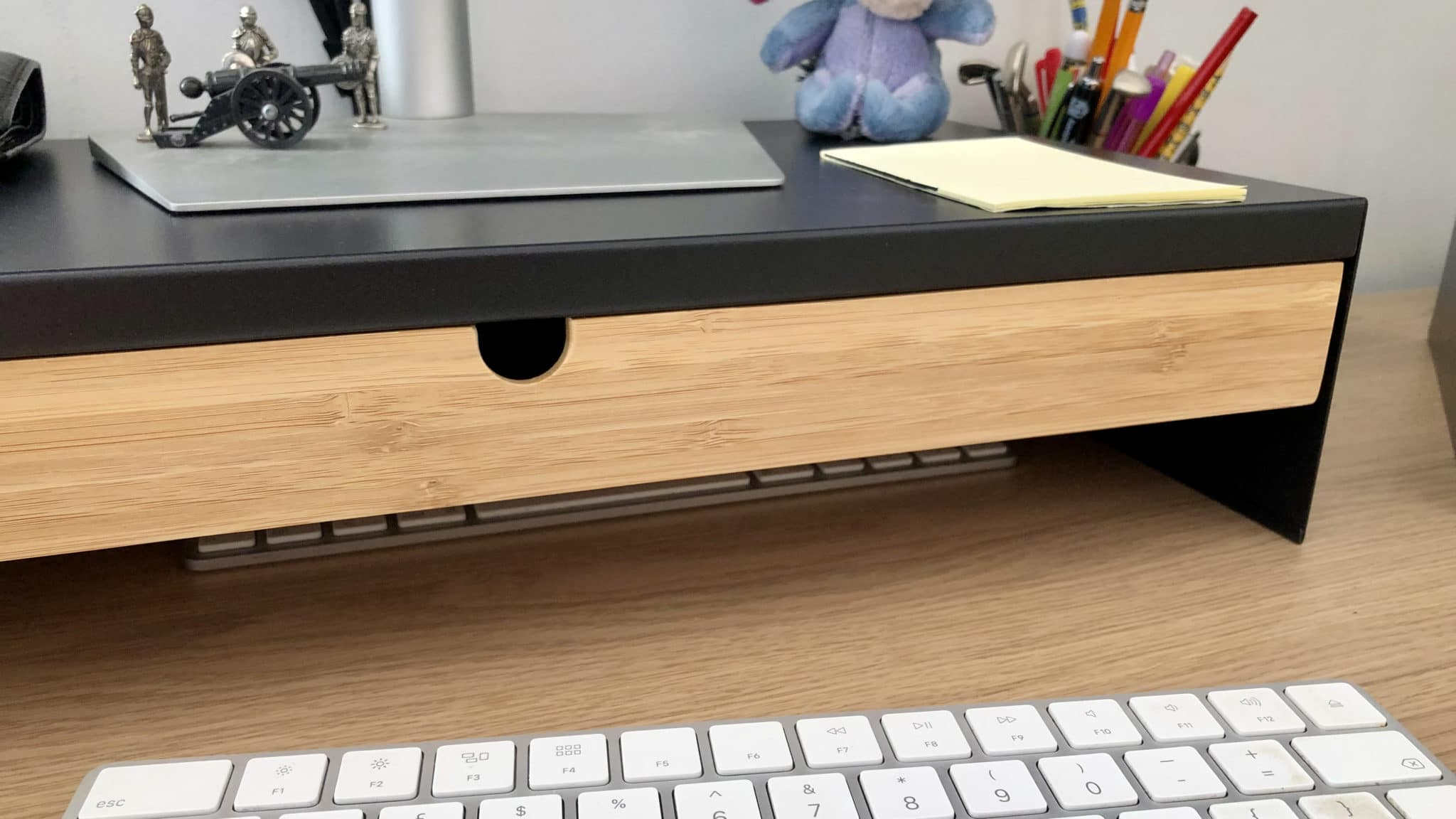 Close up of home office desk including keyboard and monitor stand.